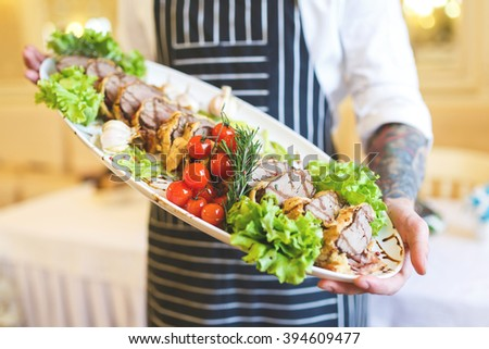 Chef holding the dish with meat in restaurant - stock photo