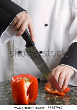 Chef in Black and White Uniform Cutting a Red Pepper Reflecting in Stove Top - stock photo