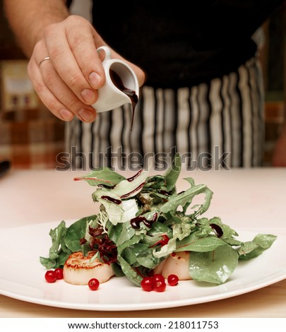 Chef is adding vinegar in appetizer with scallops, toned image - stock photo