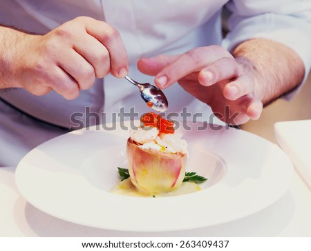 Chef is cooking a seafood appetizer, close-up, toned image - stock photo