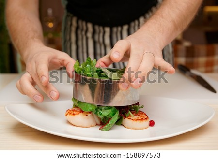 Chef is cooking appetizer with sea scallops and salad mix - stock photo