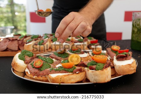 Chef is cooking bruschettas with beefsteak and pesto sauce - stock photo