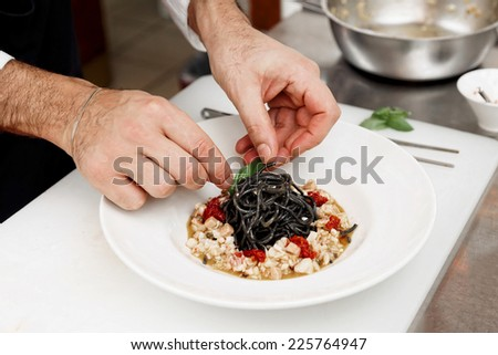 Chef is cooking pasta at commercial kitchen, toned - stock photo