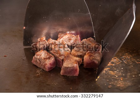 Chef is placing tenderloin steaks with kitchen tongs - stock photo