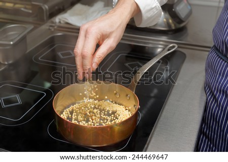 Chef is pouring fregola pasta in copper pan - stock photo