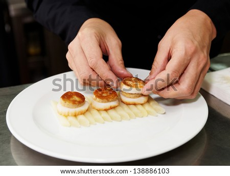 Chef is serving fried foie gras with grilled scallops - stock photo