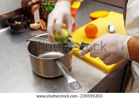 Chef is zesting lime in commercial kitchen - stock photo