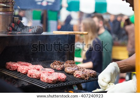 Chef making beef burgers outdoor on open kitchen international food festival event. Street food ready to serve on a food stall. - stock photo