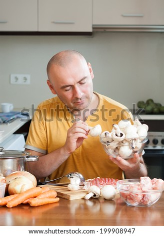 Chef man in orange t-shirt in the kitchen - stock photo