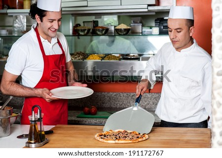 Chef placing freshly baked pizza on the table - stock photo