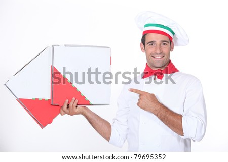 Chef pointing at pizza boxes - stock photo