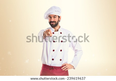 Chef pointing to the front over ocher background - stock photo