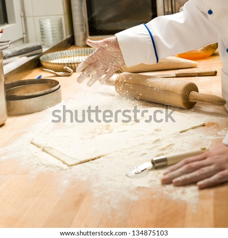 Chef pouring flour to dough and rolling pin wooden table - stock photo