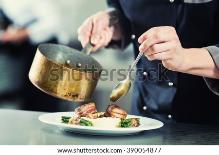 Chef pouring sauce on dish in restaurant kitchen, crop on hands, filtered image - stock photo