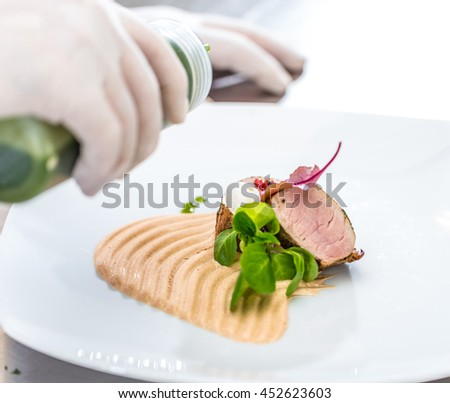 Chef pouring sauce over the meat before serving - stock photo