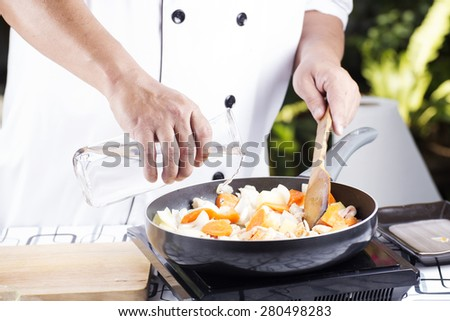 Chef pouring soup to the pan for cooking Japanese pork curry / cooking Japanese pork curry paste concept  - stock photo