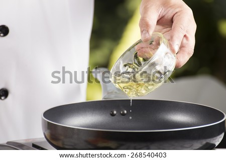 Chef pouring vegetable oil to the pan / cooking Japanese pork curry concept - stock photo