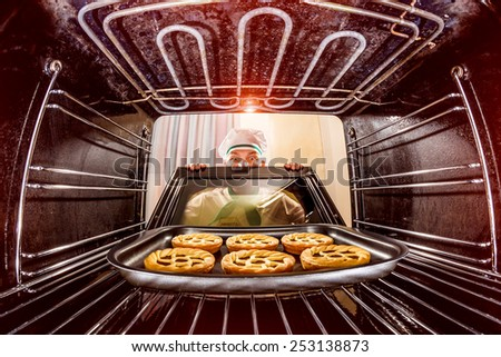 Chef prepares pastries in the oven, view from the inside of the oven. Cooking in the oven. - stock photo