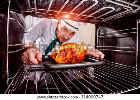 Chef prepares roast chicken (focus on chicken) in the oven, view from the inside of the oven. Cooking in the oven.Thanksgiving Day. - stock photo
