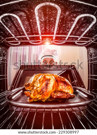 Chef prepares roast chicken in the oven, view from the inside of the oven. Cooking in the oven. - stock photo