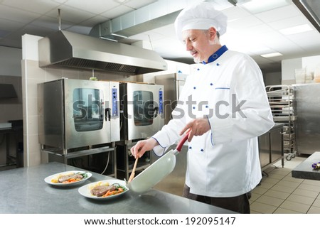 Chef preparing a dish in his kitchen - stock photo