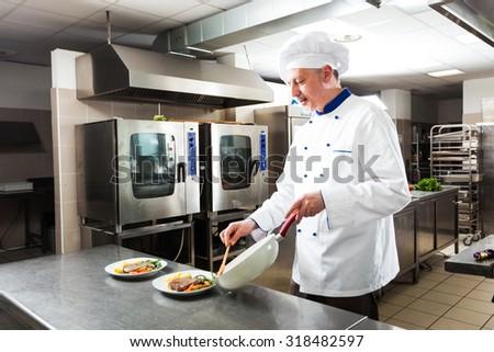 Chef preparing a dish in his kitchen - stock photo