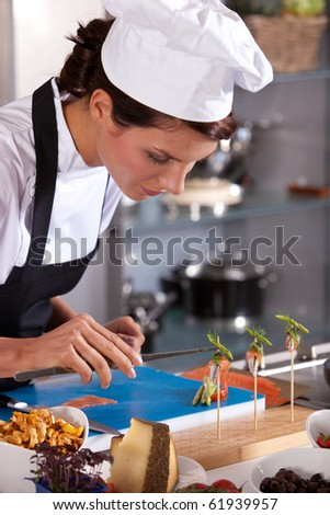 Chef preparing an amuse very carefully with pincers - stock photo
