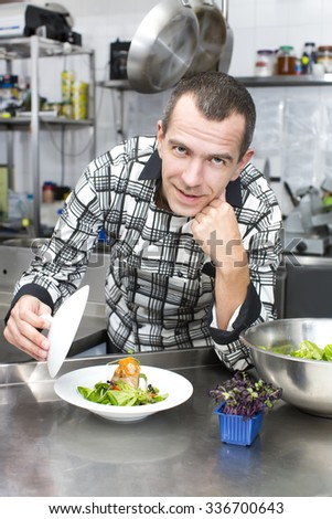 chef preparing food in the kitchen at the restaurant - stock photo