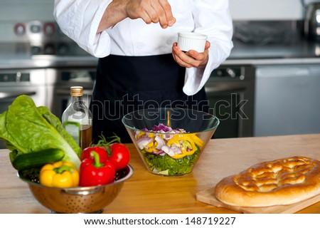 Chef preparing fresh vegetable salad - stock photo