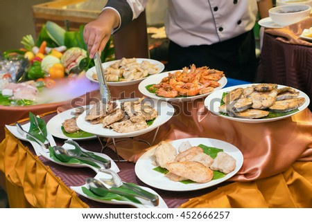 chef preparing plates of various meat, pork, beef, chicken, fish, shrimp and squid for dinner in a luxury restaurant.  - stock photo