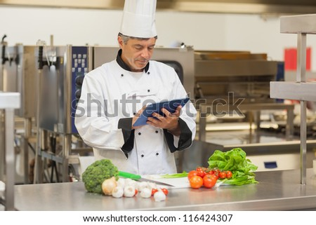 Chef preparing recipe with digital tablet in the kitchen - stock photo