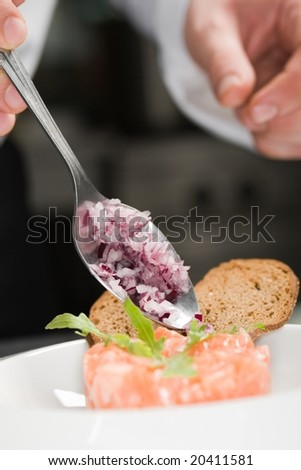 Chef preparing salmon salad - stock photo