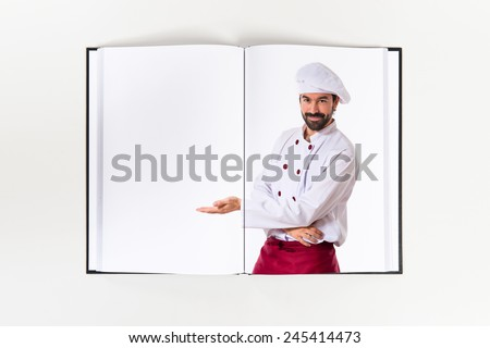 Chef presenting something printed on book - stock photo