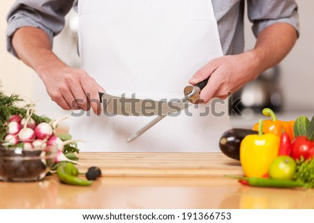 Chef. Professional chef sharpening knife inlcluding assorted fresh vegetables - stock photo