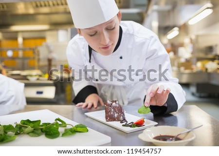 Chef putting mint with her chocolate cake in the kitchen - stock photo