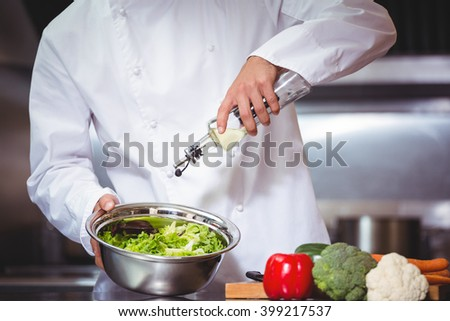Chef putting oil on salad in commercial kitchen - stock photo