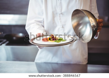 Chef raising a bell of a dish in commercial kitchen - stock photo