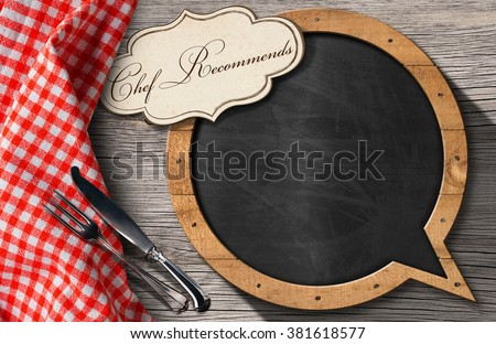 Chef Recommends - Blackboard Speech Bubble Shaped / Blackboard in the shape of speech bubble and label with text Chef Recommends and silver cutlery on a wooden table with a checkered tablecloth  - stock photo