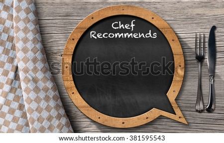 Chef Recommends - Blackboard Speech Bubble Shaped / Blackboard in the shape of speech bubble with text Chef Recommends and silver cutlery on a wooden table with a checkered tablecloth - stock photo
