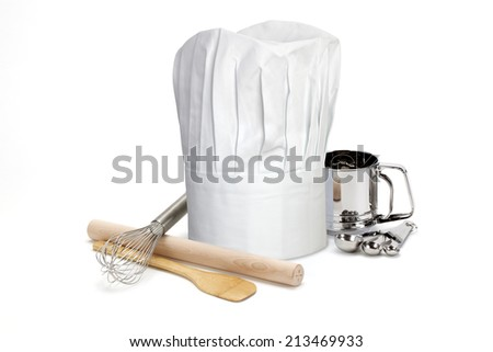 Chef's hat on white with cooking utensils - stock photo