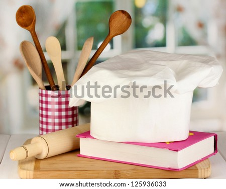 Chef's hat with battledore and cook book on board on wooden table on window background - stock photo