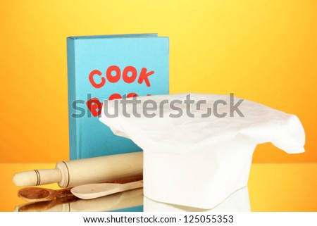 Chef's hat with battledore and cook book on orange background - stock photo