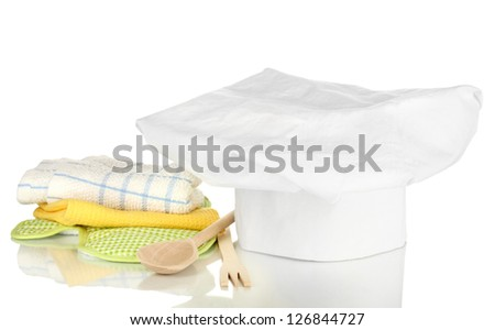 Chef's hat with kitchen towels, potholders and kitchenware isolated on white - stock photo