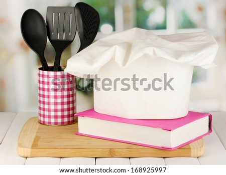 Chef's hat with spoons and cook book on board on wooden table on window background - stock photo