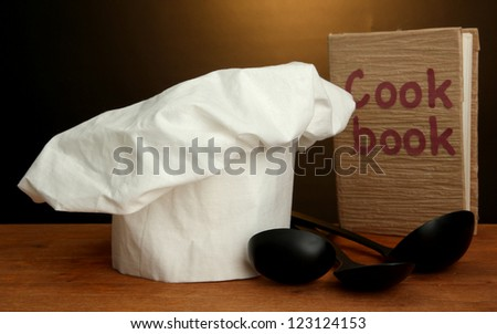 Chef's hat with spoons and cookbook on table on brown background - stock photo
