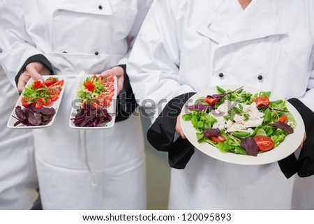 Chef's holding out their salads in kitchen - stock photo