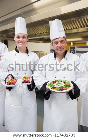 Chef's presenting their salads in the kitchen - stock photo