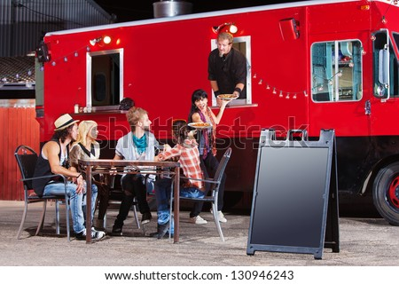 Chef serving food at mobile restaurant with blank sign - stock photo
