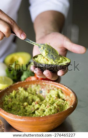 Chef serving guacamole with a spoon - stock photo