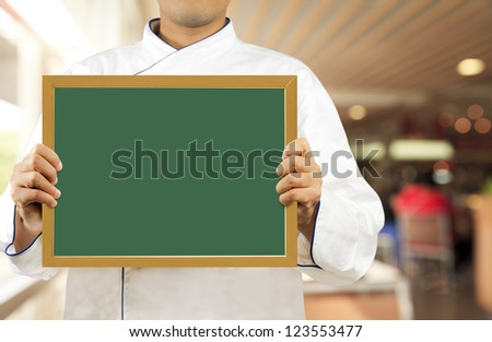 Chef showing chalkboard in the restaurant - stock photo